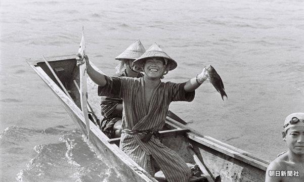 2.とれた魚を笑顔で掲げる漁師(1935年頃の沖縄)