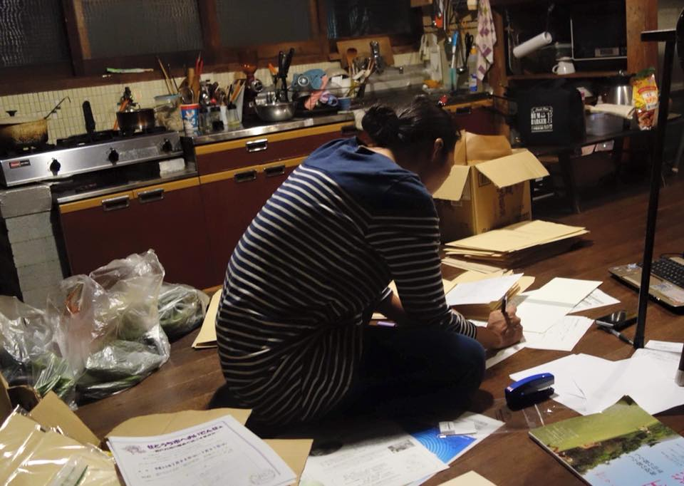 寝間着姿のまま台所で発送作業をする謎の女。